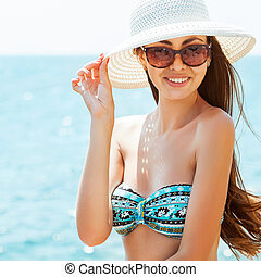 Young beautiful woman on the beach, wearing a hat