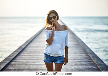 Young beautiful woman on the pier
