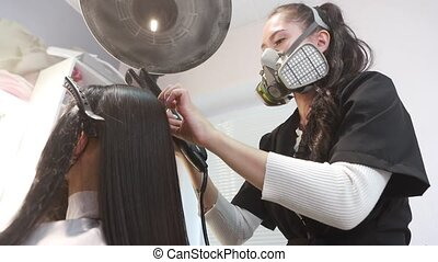 Young beautiful woman on the procedure of keratin hair treatment. Young woman hairdresser in a protective respirator works with hair in the salon. Hair treatment and restoration concept