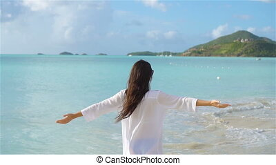 Young beautiful woman on tropical seashore. Happy girl background the blue sky and turquoise water in the sea on caribbean island.