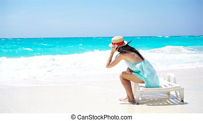 Young beautiful woman on white sand tropical beach. Back view of caucasian girl in hat background the sea