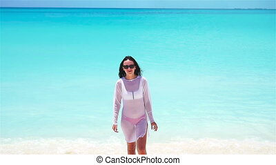 Young beautiful woman on white tropical beach. Girl having fun on her summer vacation. SLOW MOTION