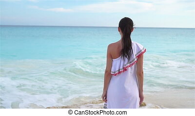 Young beautiful woman on white tropical beach. Girl walking by the sea. SLOW MOTION