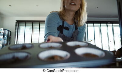 Young beautiful woman opens the oven and puts in baking tray. Attractive female cooking cupcakes in the kitchen.