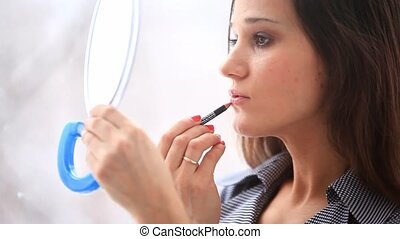 Young beautiful woman paints her lips looking in the mirror on white bakground. HD. 1920x1080