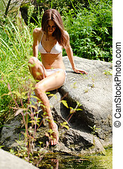 Young beautiful woman playing in wild river