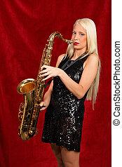 Young beautiful woman playing saxophone - Young blonde woman...