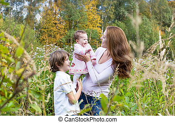 Young beautiful woman playing with her son and daughter in a col