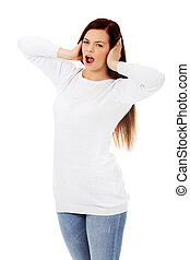 Young beautiful woman plugging her ears and screaming