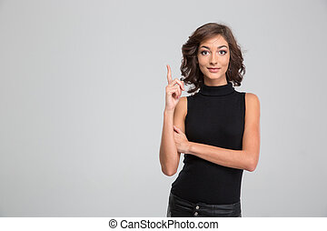 Young beautiful woman pointing up and having an idea