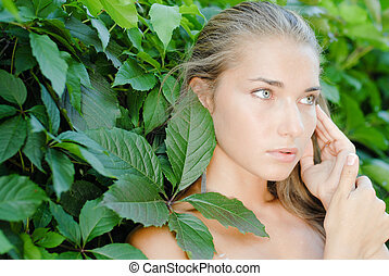 Young beautiful woman portrait among green leaves of virginia creeper