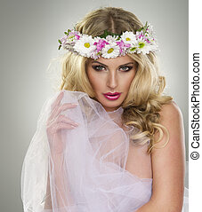 young beautiful woman portrait with wreath of flowers studio shot