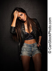 Young beautiful woman posing in black leather jacket