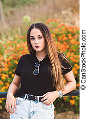 Young beautiful woman posing in flowers field