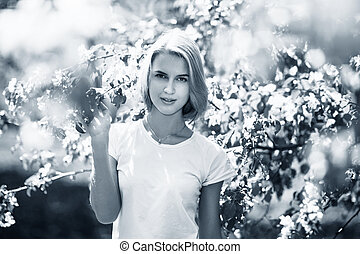 Young beautiful woman posing in the green park.