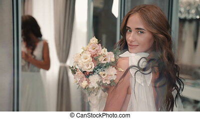 Young beautiful woman posing in wedding dress while standing in light studio. Closeup view of attractive girl model looking at camera with happy smile and holding bouquet of flowers in her hands at modern interior. Pretty brunette poses for fashion shoot indoors. Concept: person, beauty, glamour.
