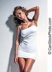 Young beautiful woman posing in white dress
