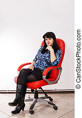young beautiful woman posing sitting on a red chair