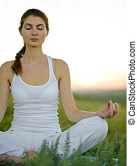 Young Beautiful Woman Practices Yoga on the Meadow