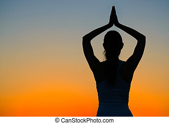 Young Beautiful Woman Practices Yoga on the Sunset