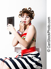 young beautiful woman preparing to party, girl styling hair with curlers looking in the mirror retro style