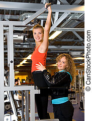 Young beautiful woman pulls herself up with assistance of personal trainer
