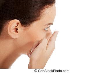 Young beautiful woman putting contact lens.