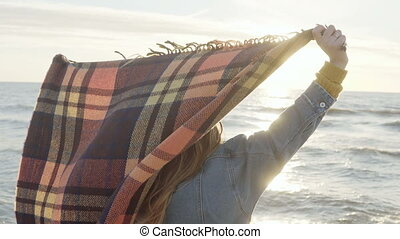 Young beautiful woman raises hands up with plaid on the shore of the sea. Happy female enjoying the sunset on the beach.