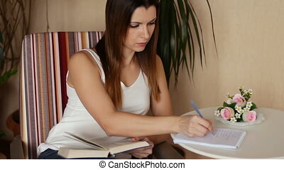 Young beautiful woman reading a book and taking notes. Woman reading a book sitting in a chair.