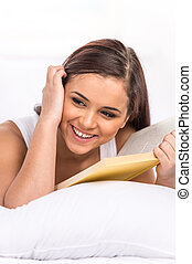 young beautiful woman reading book. pretty girl lying in her bed at home