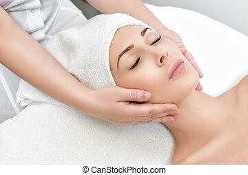 woman receiving facial massage at spa salon