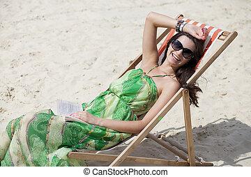 Young beautiful woman relaxing lying on a sun lounger