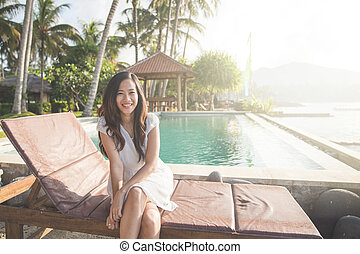 woman relaxing next to the pool