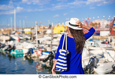Young beautiful woman relaxing on dock near the boat on sunny day
