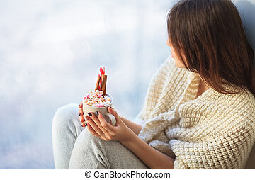 Young beautiful woman relaxing with cup of hot chocolate on window sill