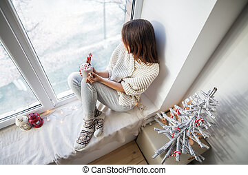 Young beautiful woman relaxing with hot coffee on window sill in christmas decorated home