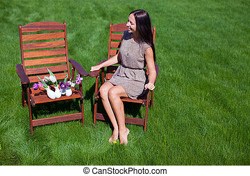 Young beautiful woman resting and have fun in the yard