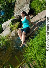 Young beautiful woman resting by river