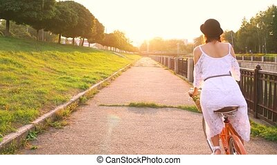 Young beautiful woman riding a bicycle at sunset. Slow motion