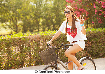 Young beautiful woman riding bicicle on summer