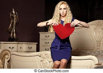 young beautiful woman rips a paper heart