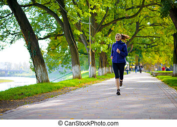 Young Beautiful Woman Running in the Autumn Park