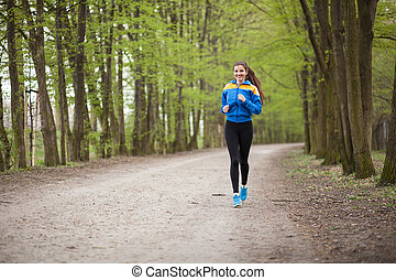 Young beautiful woman running on a trail