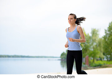 Young Beautiful Woman Running on the Beach Trail in the Morning
