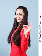 Young beautiful woman shows OK sign