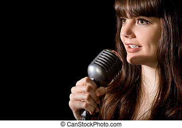 young beautiful woman sing in microphone isolated on black background