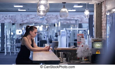 Young beautiful woman sit at bar in gym and drink protein cocktail.