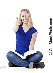 Young beautiful woman sits cross-legged and holds thumb...