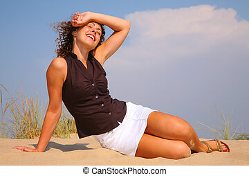Young beautiful woman sits on sand