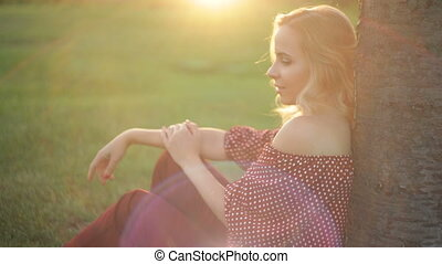 Young beautiful woman sits under a tree on the grass in sunset